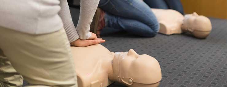 Kursusdeltager lærer førstehjælp og giver hjertemassage på øvelsesdukke ved førstehjælpskursus